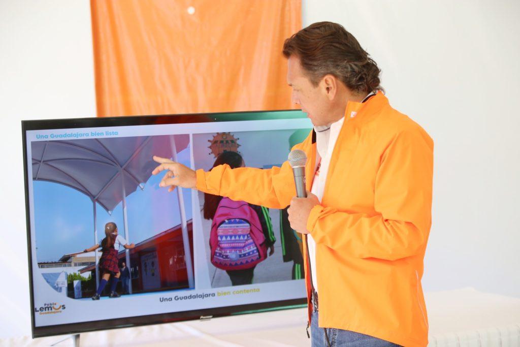 Pablo Lemus Navarro, candidato a la presidencia municipal de Guadalajara, mostrando la propuesta Guadalajara bien contenta con una pantalla donde se ven niños en entornos escolares