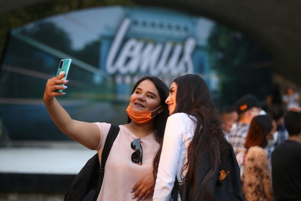 Dos mujeres en el evento Lemus Unplugged en la concha acústica de Guadalajara, tomándose una foto.